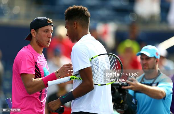 Felix AugerAliassime of Canada is congratulated by Lucas Pouille of France following a 1st round match on Day 2 of the Rogers Cup at Aviva Centre on...