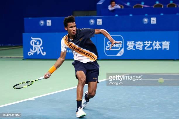 Felix AugerAliassime of Canada returns a shot during his match against Bernard Tomic of Australia during 2018 ATP World Tour Chengdu Open at Sichuan...