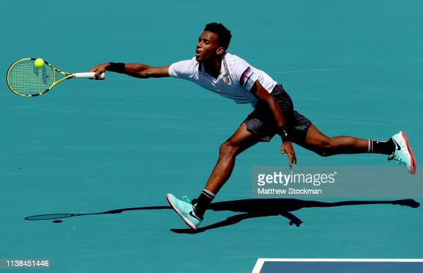 Felix AugerAliassime of Canada stretches for a ball while playing Nikoloz Basilashvili of Georgia during the Miami Open Presented by Itau at Hard...