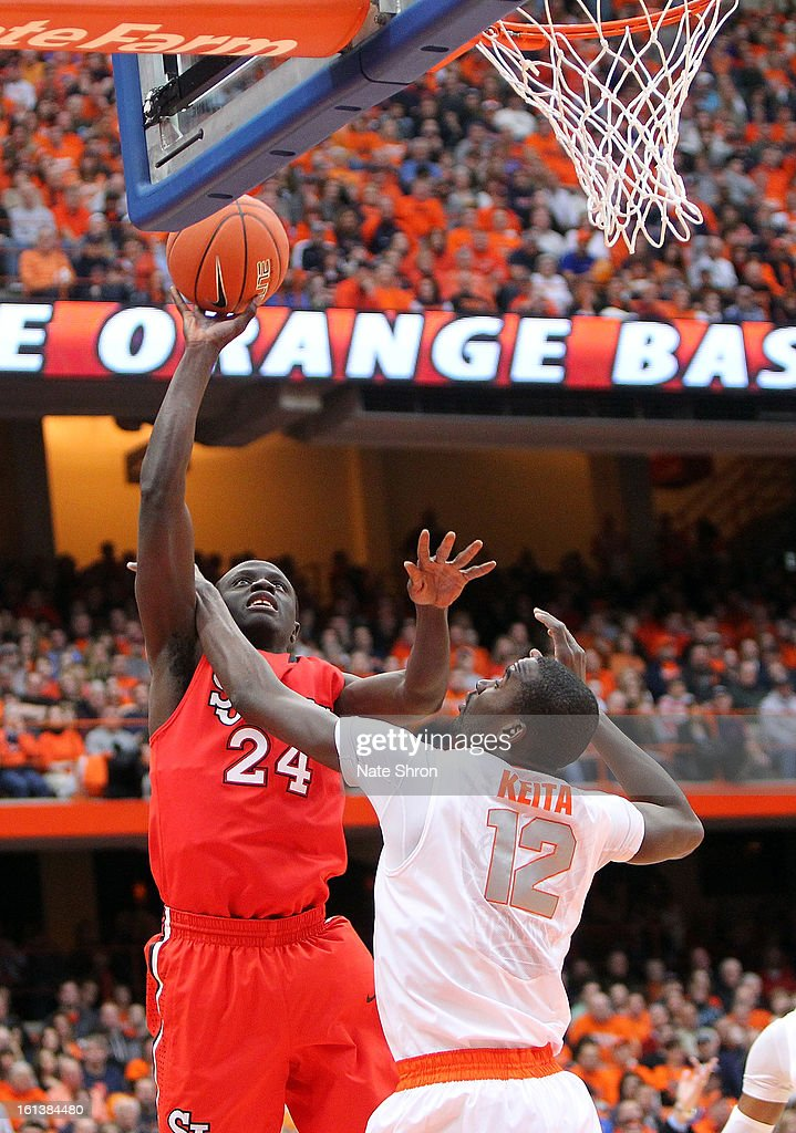 Felix Balamou #24 of the St. John's Red Storm puts the ball up to the basket against Baye Moussa Keita #12 of the Syracuse Orange during the game at the Carrier Dome on February 10, 2013 in Syracuse, New York.