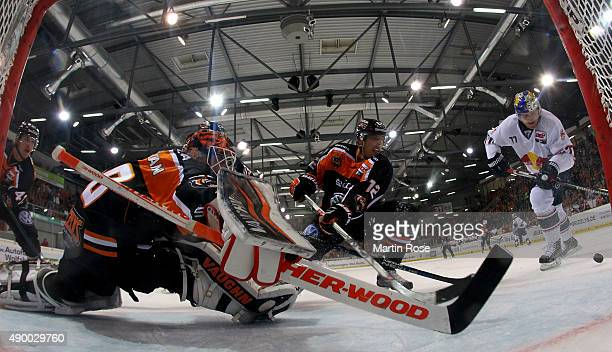 Felix Brueckmann goaltender of Wolfsburg makes a save on Ulrich Maurer of Muenchen during the DEL match between Grizzly Adams Wolfsburg and EHC Red...