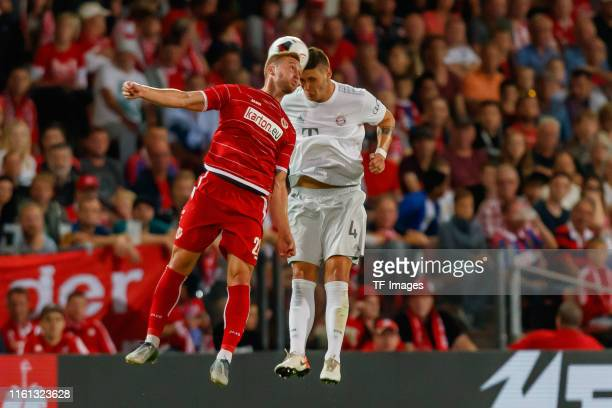 Felix Bruegmann of Energie Cottbus and Niklas Suele of FC Bayern Muenchen battle for the ball during the DFB Cup first round match between Energie...