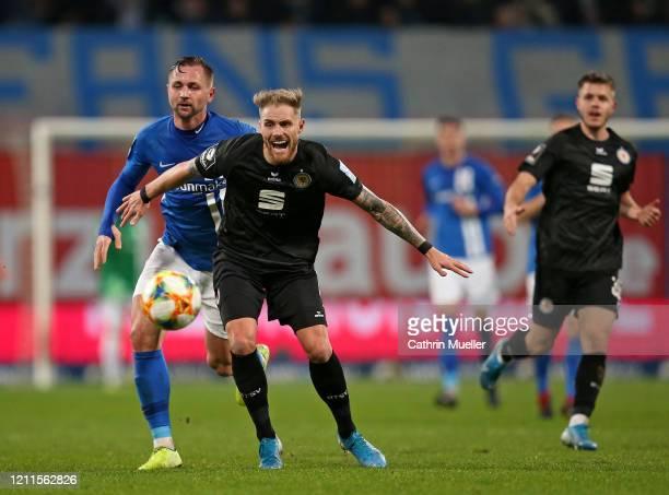 Felix Burmeister of Eintracht Braunschweig and John Verhoek of Hansa Rostock battle for the ball during the 3 Liga match between Hansa Rostock and...