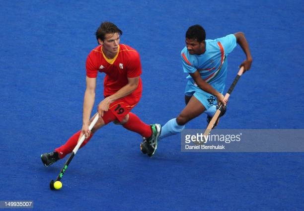 Felix Denayer of Belgium and Birendra Lakra of India challenge for the ball during the Men's Hockey match between Belgium and India on Day 11 of the...