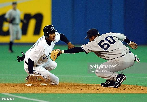 Felix Escalona of the New York Yankees is comes up short on the tag of Eric Crozier of the Toronto Blue Jays in MLB action at Skydome October 1 2004...