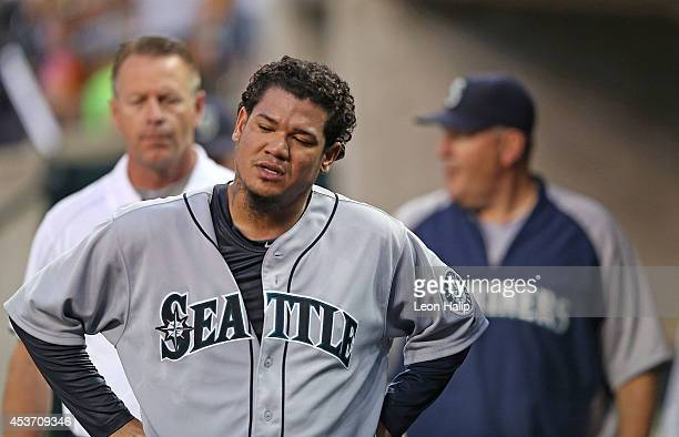 Felix Hernandez of the Seattle Mariners reacts in the dugout after getting hit in the leg by a line drive from Ian Kinsler of the Detroit Tigers...