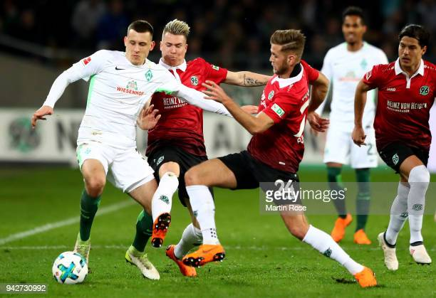 Felix Klaus and Niclas Fuellkrug of Hannover and Maximilian Eggestein of Bremen battle for the ball during the Bundesliga match between Hannover 96...