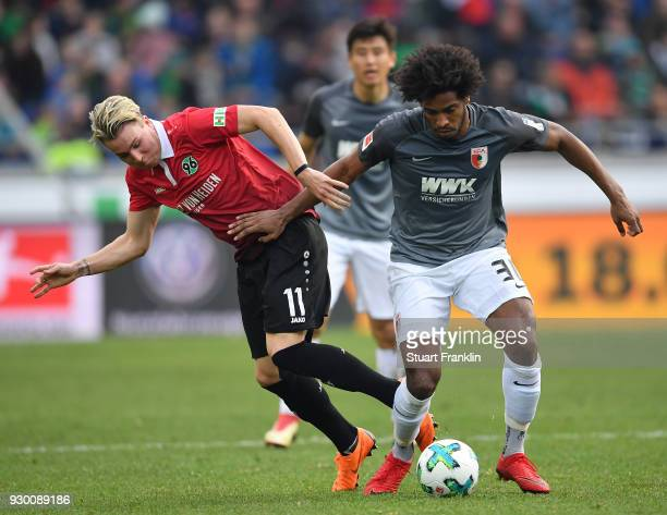 Felix Klaus of Hannover is challenged by Caiuby of Augsburg during the Bundesliga match between Hannover 96 and FC Augsburg at HDIArena on March 10...