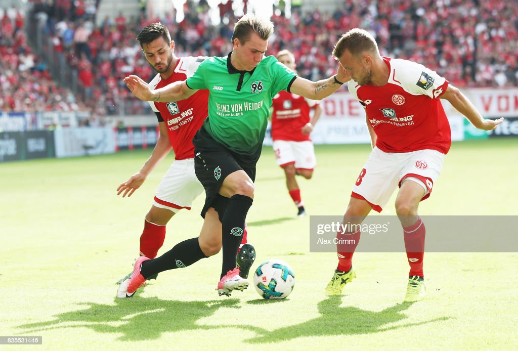 Felix Klaus (C) of Hannover is challenged by Daniel Brosinski (R) and Danny Latza of Mainz during the Bundesliga match between 1. FSV Mainz 05 and Hannover 96 at Opel Arena on August 19, 2017 in Mainz, Germany.