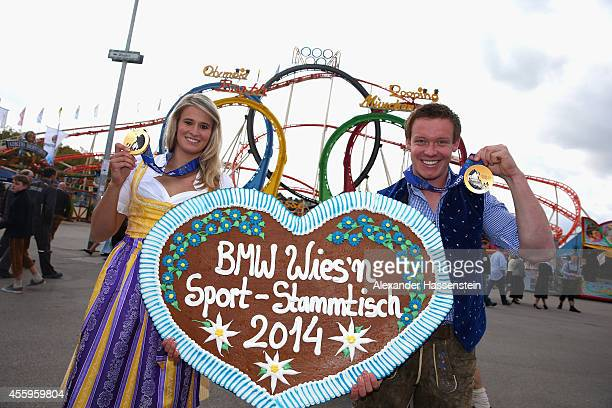 Felix Loch and Natalie Geisenberger present their Sochi 2014 Olympic Gold medals in front of the 'Olympia Looping' rooler coaster during the 'BMW...