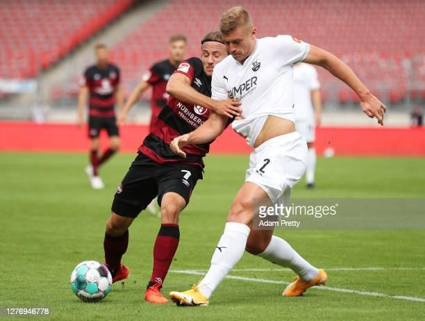 Felix Lohkemper of 1. FC Nuernberg challenges Aleksandr Zhirov of SV Sandhausen during the Second Bundesliga match between 1. FC Nürnberg and SV...