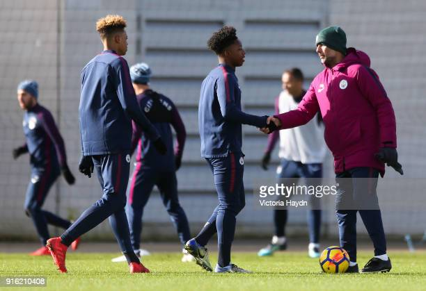 Felix Nmecha and Keke Simmonds shake hands with Pep Guardiola during training at Manchester City Football Academy on February 9 2018 in Manchester...