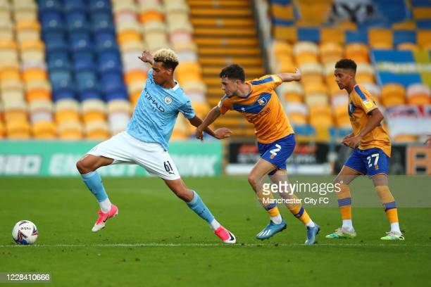 Felix Nmecha of Manchester City in action with Corey O'Keeffe and Tyrese Sinclair of Mansfield Town during the EFL Trophy match between Mansfield...