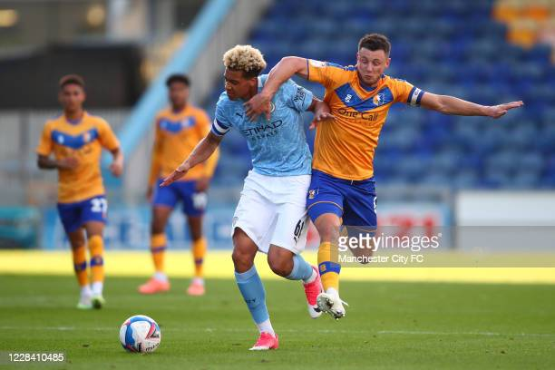 Felix Nmecha of Manchester City in action with Ollie Clarke of Mansfield Town during the EFL Trophy match between Mansfield Town and Manchester City...
