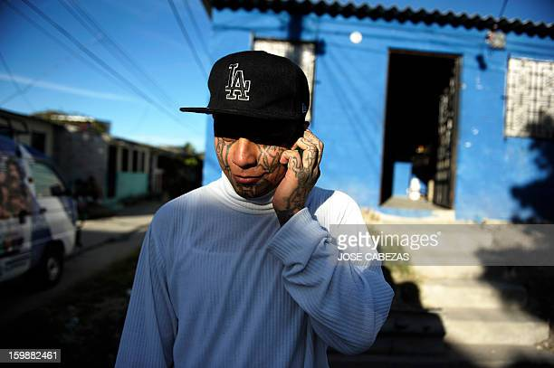 Felix of the 18th street gang talks on the phone outside a bakery operated by gang members as a part of a rehabilitation program in San Bartolo...