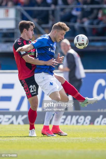 Felix Platte of Darmstadt is challenged by MarcOliver Kempf of Freiburg during the Bundesliga match between SV Darmstadt 98 and SC Freiburg at...