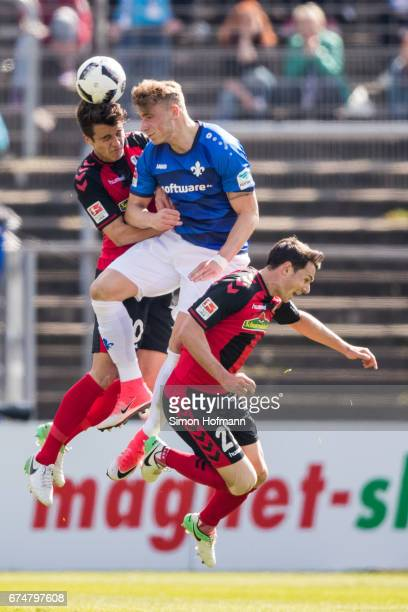 Felix Platte of Darmstadt jumps for a header with MarcOliver Kempf and Nicolas Hoefler of Freiburg during the Bundesliga match between SV Darmstadt...