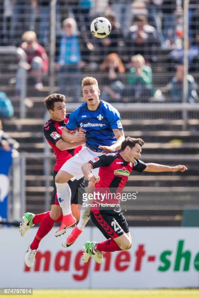 Felix Platte of Darmstadt jumps for a header with MarcOliver Kempf and Nicolas Hoefler of Freiburg during the Bundesliga match between SV Darmstadt...