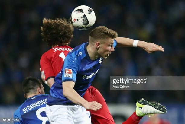 Felix Platte of Darmstadt jumps for a header with Tin Jedvaj of Leverkusen during the Bundesliga match between SV Darmstadt 98 and Bayer 04...