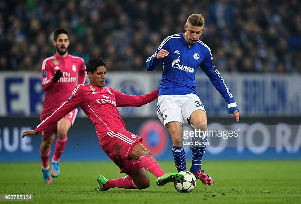 Felix Platte of Schalke is tackled by Raphael Varane of Real Madrid during the UEFA Champions League Round of 16 match between FC Schalke 04 and Real...