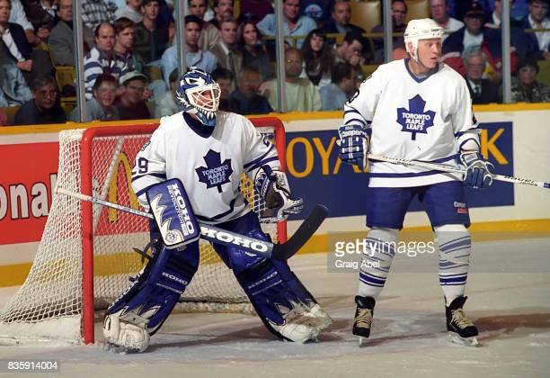 Felix Potvin and Todd Gill of the Toronto Maple Leafs skate against the Colorado Avalanche during NHL preseason game action on September 27 1995 at...