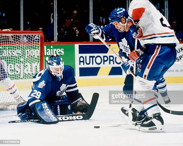 Felix Potvin of the Toronto Maple Leafs looks for the loose puck near the net during a game against the Montreal Canadiens Circa 1993 at the Montreal...