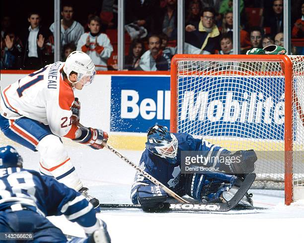 Felix Potvin of the Toronto Maple Leafs robs Guy Carbonneau of the Montreal Canadiens with a left pad save during a game Circa 1993 at the Montreal...