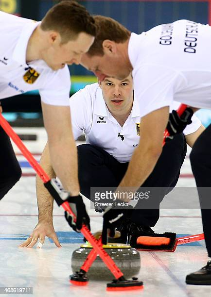 Felix Schlze of Germany looks on with teammates Sven Goldemann and Christopher Bartsch as they compete in the men's round robin session against Great...