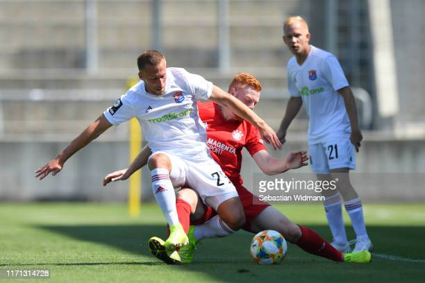 Felix Schroeter of Unterhaching and Paul Willof Bayern Muenchen II compete for the ball during the 3. Liga match between Bayern Muenchen II and...