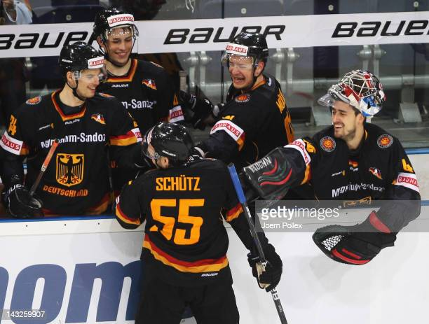 Felix Schuetz of Germany jokes with his team mates after scoring his team's fourth goal during the international friendly icehockey match between...