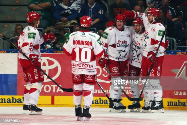 Felix Schuetz of Koeln celebrates his team's third goal with team mates during the DEL match between Adler Mannheim and Koelner Haie at SAP Arena on...