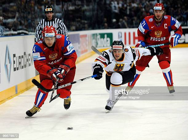Felix Schultz of Germany battles for the puck with Alexander Frolov of Russia during the IIHF World Championship qualification round match between...
