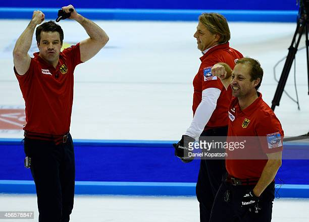 Felix Schulze of Germany and team mates John Jahr and Sven Goldemann celebrate after the Olympic Qualification Tournament playoff match between...