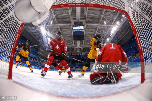 Felix Schutz and Matthias Plachta of Germany celebrate a goal by Leonhard Pfoderl in the first period against Jonas Hiller of Switzerland during the...