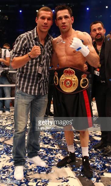 Felix Sturm of Germany celebrates with German national football player Lukas Podolski after winning the WBA middleweight world championship fight...