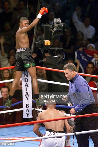 Felix Trinidad of Puerto Rico looks over his shoulder at his opponent MexicanAmerican Fernando Vargas and the referee as he celebrates after a 12th...