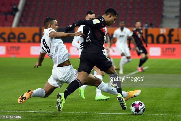 Felix Uduokhai of Augsburg battles for possession with Serge Gnabry of Bayern Munich during the Bundesliga match between FC Augsburg and FC Bayern...