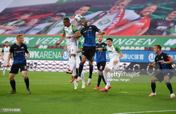 Felix Uduokhai of Augsburg jumps for a header with Klaus Gjasula of Paderborn during the Bundesliga match between FC Augsburg and SC Paderborn 07 at...