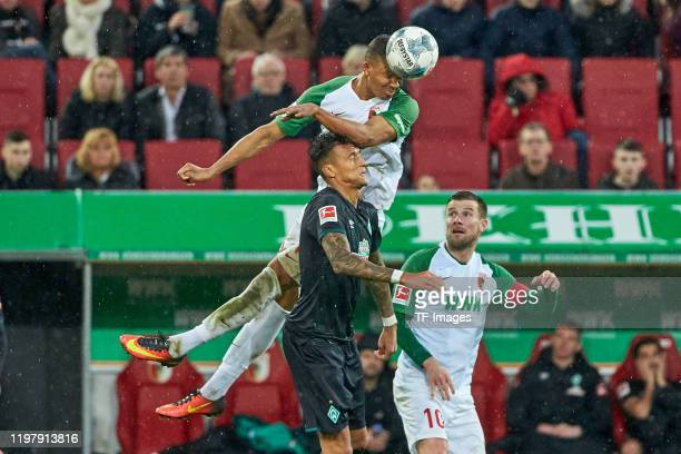 Felix Uduokhai of FC Augsburg and Davie Selke of SV Werder Bremen battle for the ball during the Bundesliga match between FC Augsburg and SV Werder...