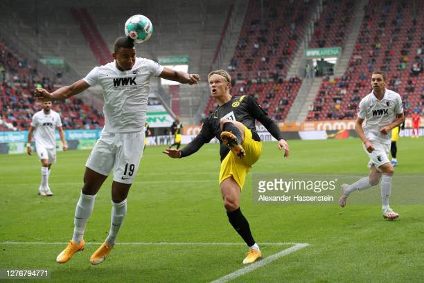 Felix Uduokhai of FC Augsburg is put under pressure by Erling Haaland of Borussia Dortmund during the Bundesliga match between FC Augsburg and...