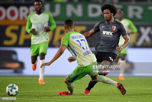 Felix Uduokhai of Wolfsburg tackles Caiuby of Augsburg during the Bundesliga match between VfL Wolfsburg and FC Augsburg at Volkswagen Arena on April...