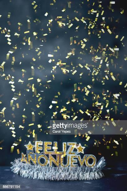 """"""" feliz año nuevo"""" message in a party tiara with confetti"""