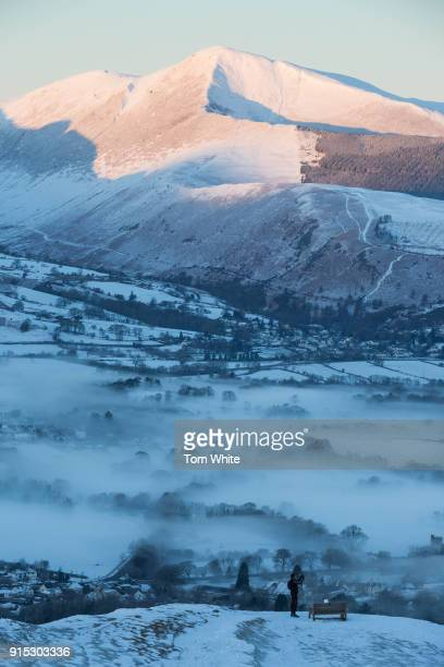 A fell runner stops to take a picture as he makes his way over Latrigg at dawn on February 7 2018 near Keswick England Freezing conditions are...