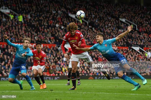 Fellaini of Manchester United wins a header over Konstantinos Mavropanos of Arsenal during the Premier League match between Manchester United and...
