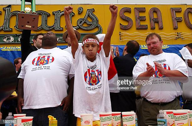 Fellow contestants applaud as twentythree yearold Takeru Kobayash of Japan raises his hands in victory July 4 2001 at the 86th annual Nathan''s...