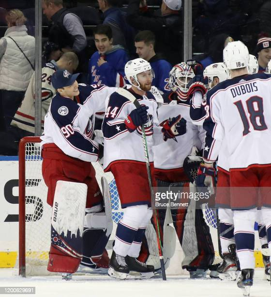 Fellow Latvia born goaltender Elvis Merzlikins of the Columbus Blue Jackets reaches in to congratulate Matiss Kivlenieks on his first NHL win in his...