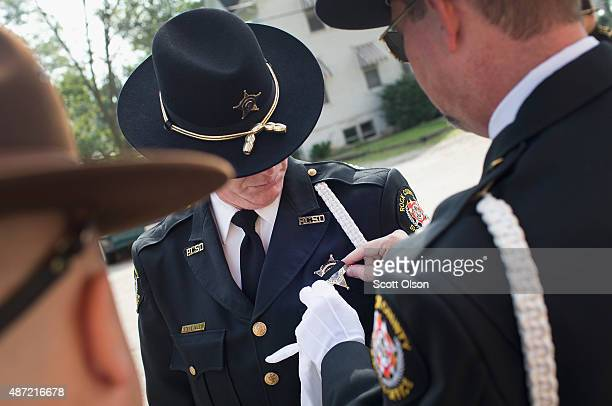 A fellow officer adjusts the mouring band on the badge of Rock County Police oficer Steve Seley as they arrive for the visitation and funeral of...