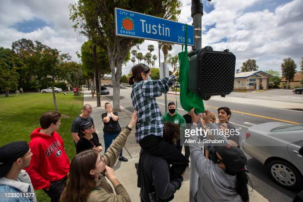 Fellow Starbucks employees and friends gather to remember and hang a Starbucks apron filled with written memorial notes on the street sign at the...