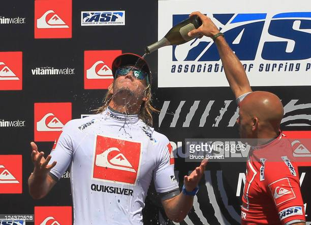 Fellow surfer Kelly Slater douses Owen Wright with champagne following Wright's victory at the Quiksilver Pro New York surfing tournament on...