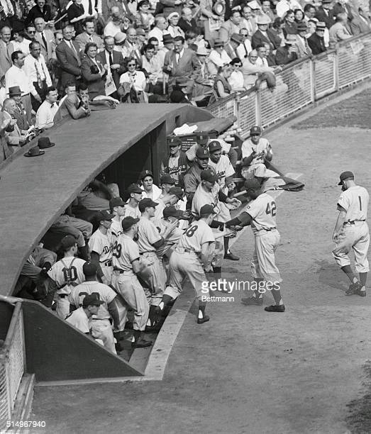 FellowDodgers are greeting Jackie Robinson of the Brooklyn Dodgers as he returned to the dugout after slapping out a homer on the first pitch to him...